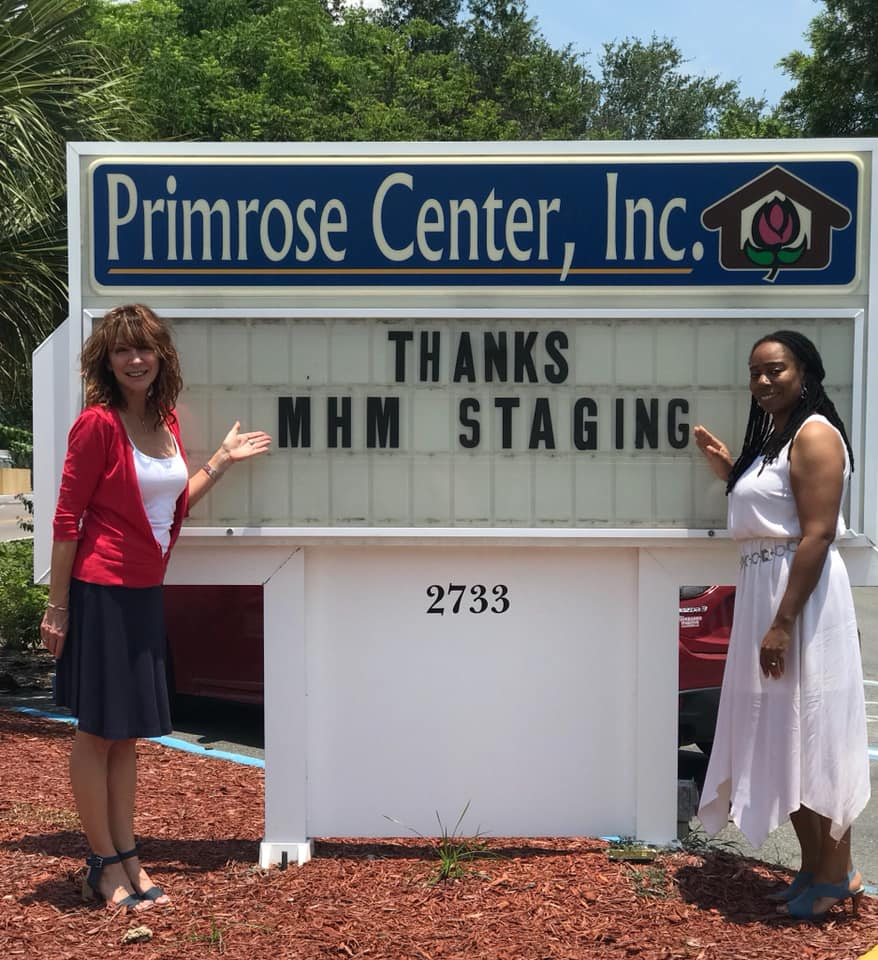 "Primrose Center staff standing next to a marquee sign that reads, ""Thanks MHM Staging"""