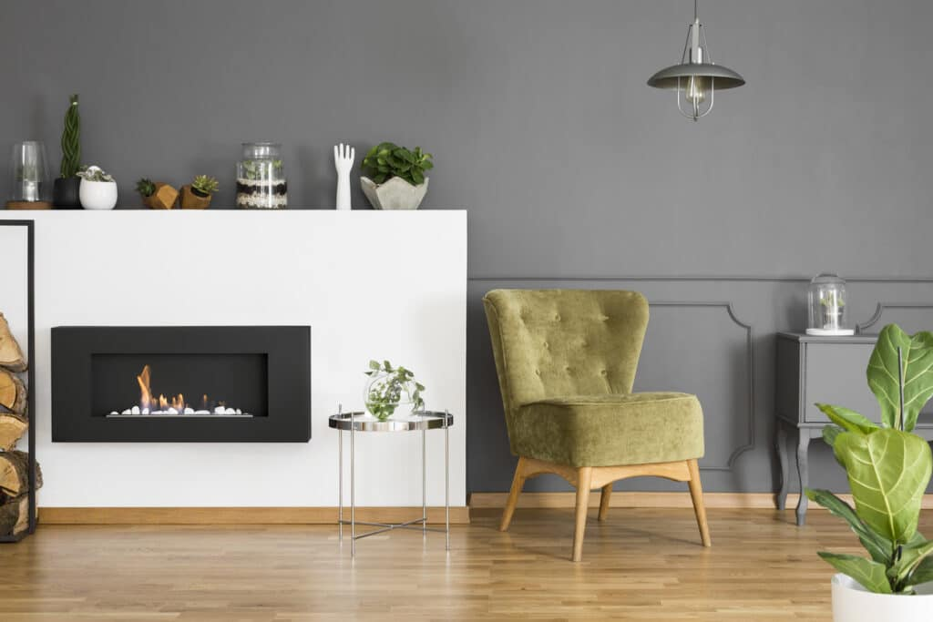 Tupelo Tree colored armchair next to fireplace in grey apartment