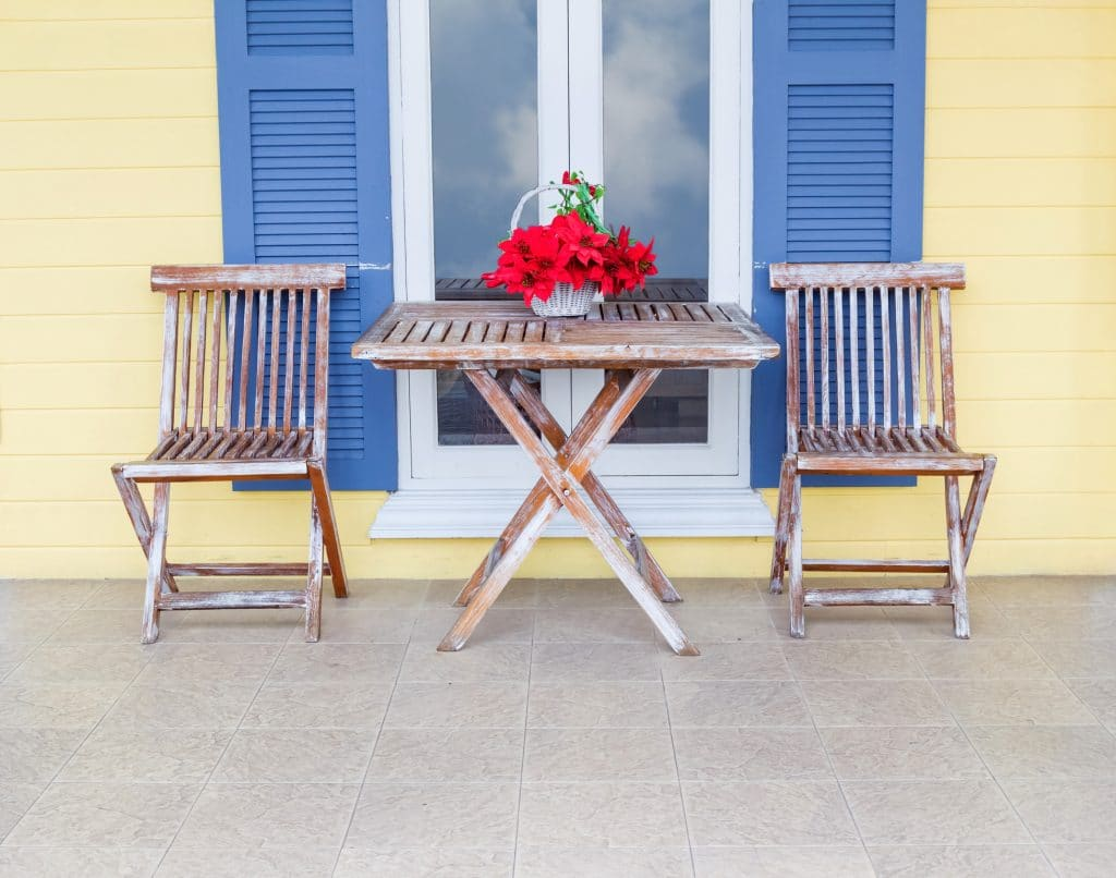 Lemon Chiffon colored house with blue shutters and worn out wooden table and chairs