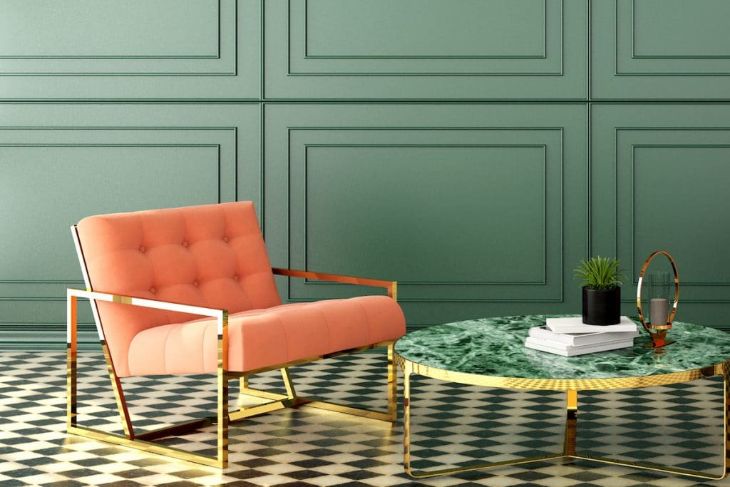 Persimmon colored chair in a green room with gold accents