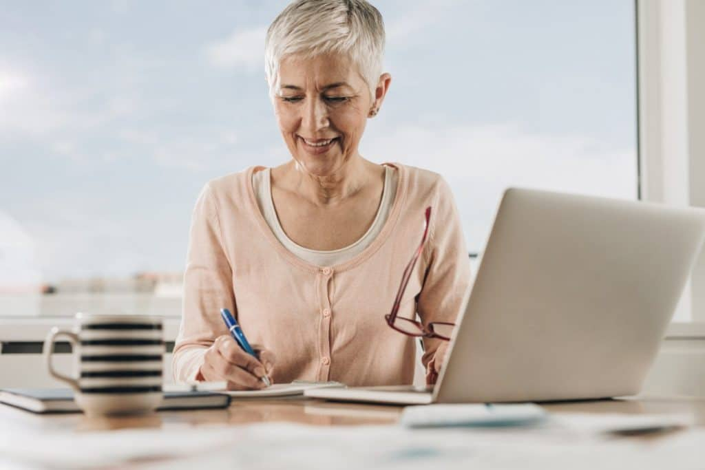 Woman in front of a laptop making a list of the 5 questions you should ask a value staging company