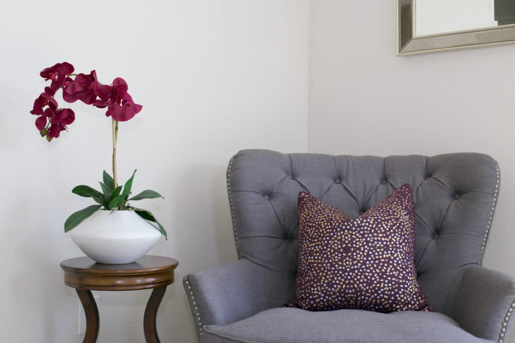 Plush armchair and side table with burgundy orchid in the Underwood style home by luxury homebuilder Toll Brothers, staged by MHM Professional Staging
