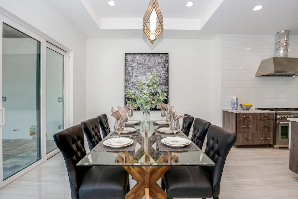 An example of professional home staging: glass dining table with black leather dining chairs