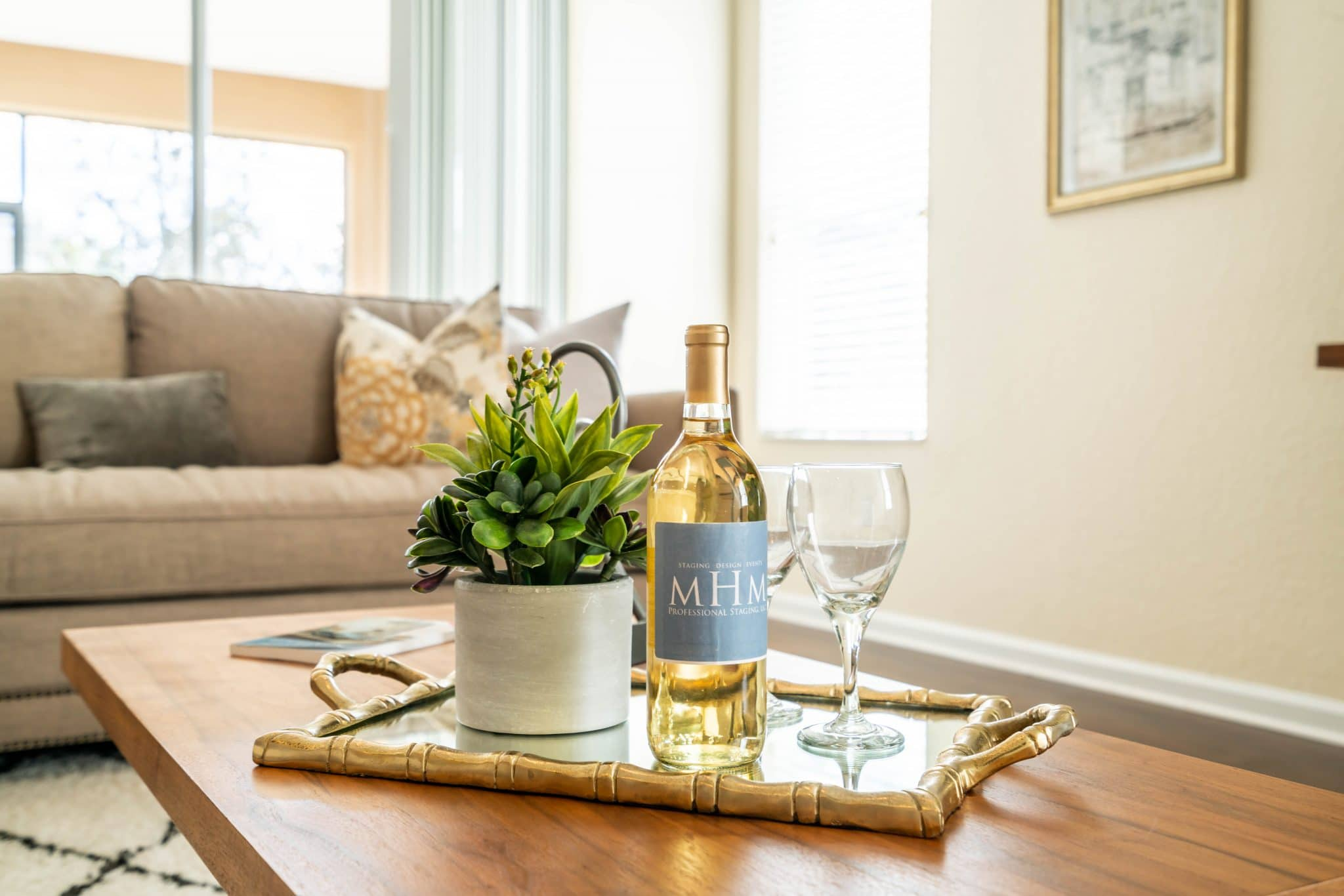 An example of soft staging: a tray with wine glasses, small plant, and bottle of wine on a coffee table