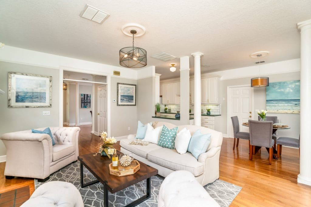 An example of professional home staging: off-white colored couch with matching arm chairs in a living room
