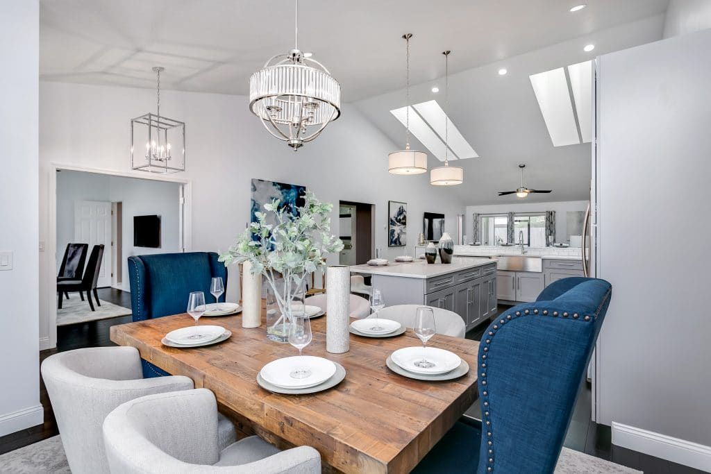 An example of professional home staging: dining table with dark blue armchairs at the ends and gray barrel chairs on the sides