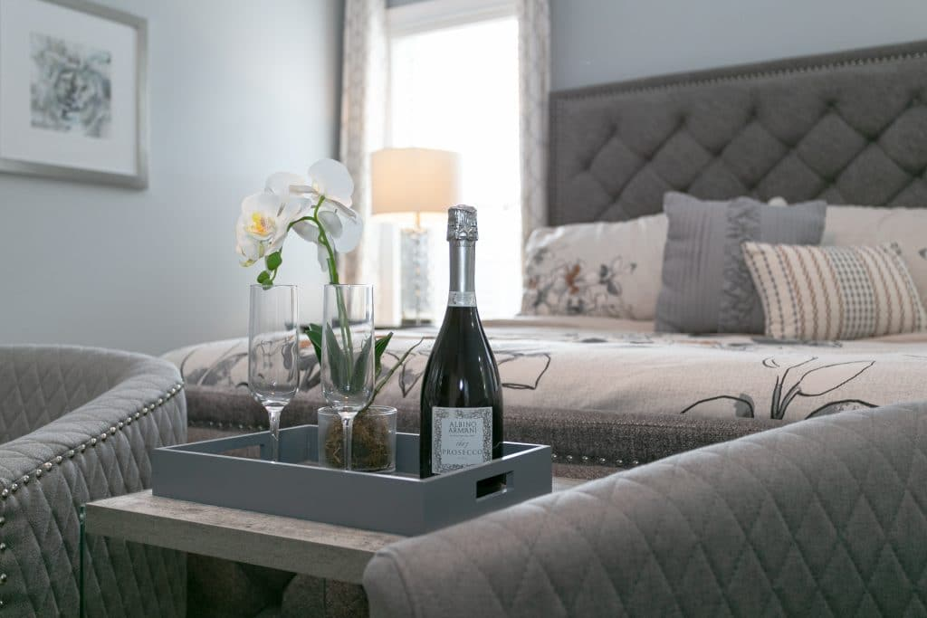 An example of professional home staging: Tray with bottle of champagne, glasses, and flowers at the foot of a bed