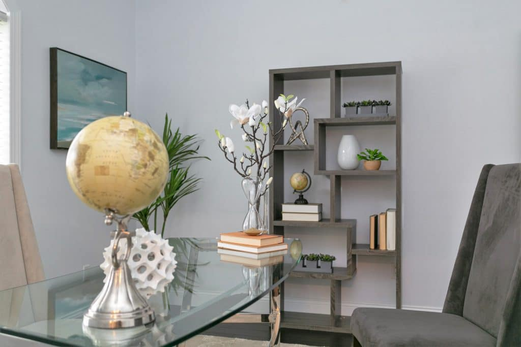 An example of professional home staging: a home office with globe, flowers, and books on the desk