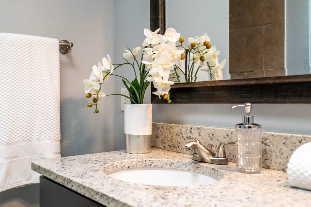 An example of professional home staging: bathroom counter with flowers and fresh white towel