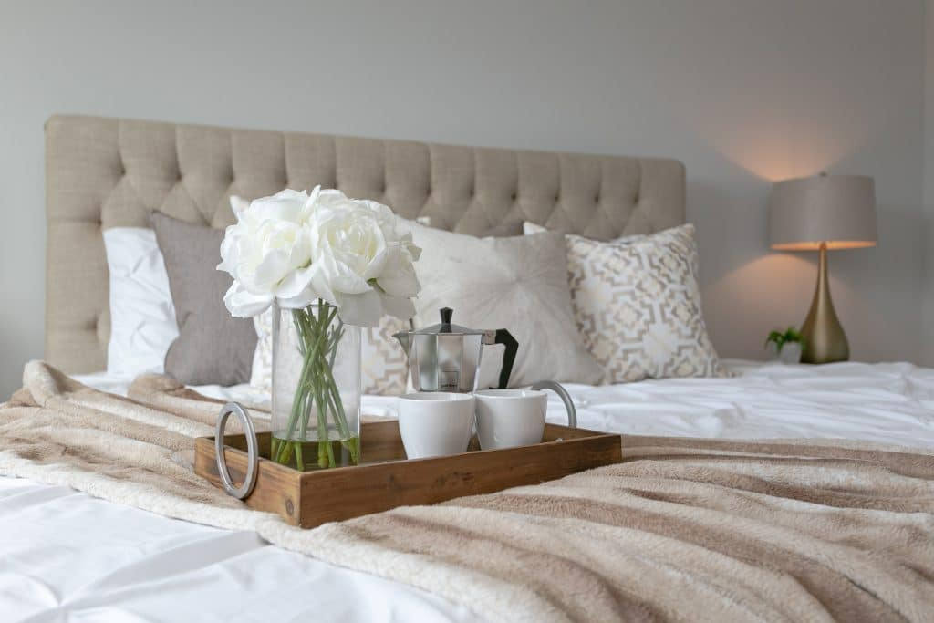 A tray with flowers, coffee pot, and mugs on a bed helping create ambiance in a bedroom