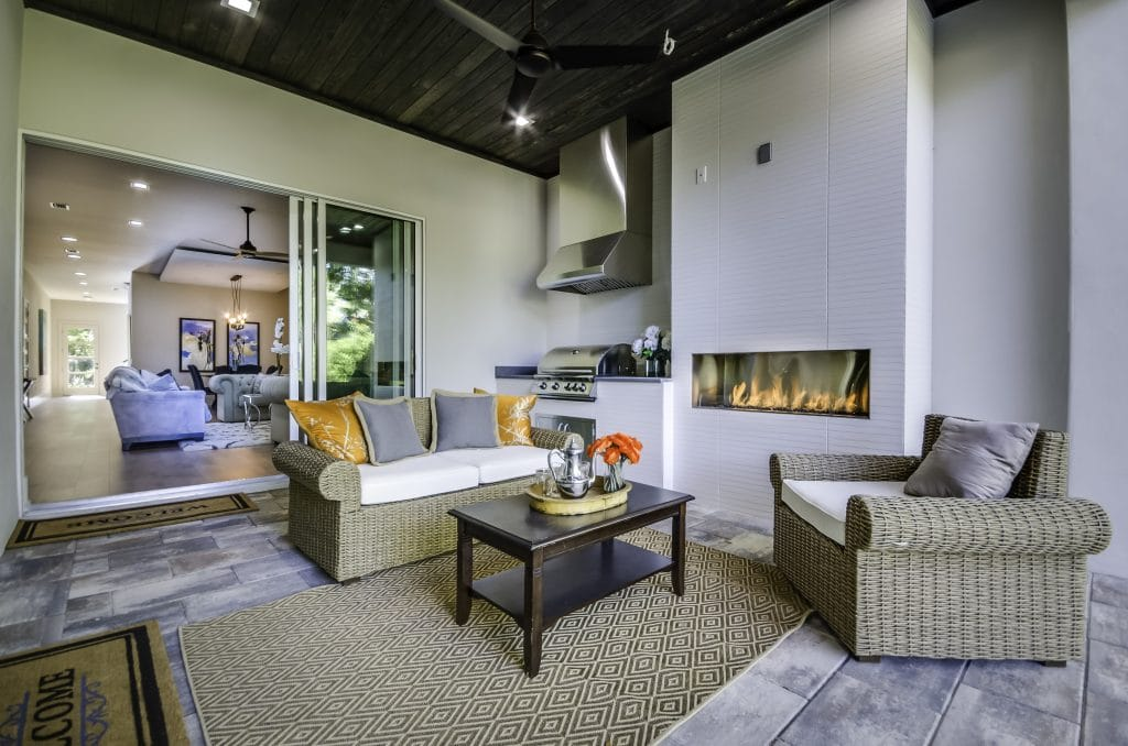A patio with outdoor fireplace staged with outdoor furniture by MHM Professional Home Staging