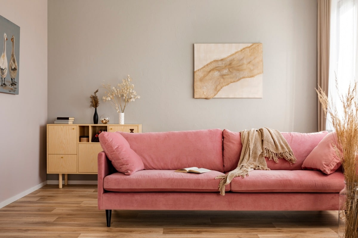 Fussy pink couch in a living room with neutral gray walls and light wood furniture