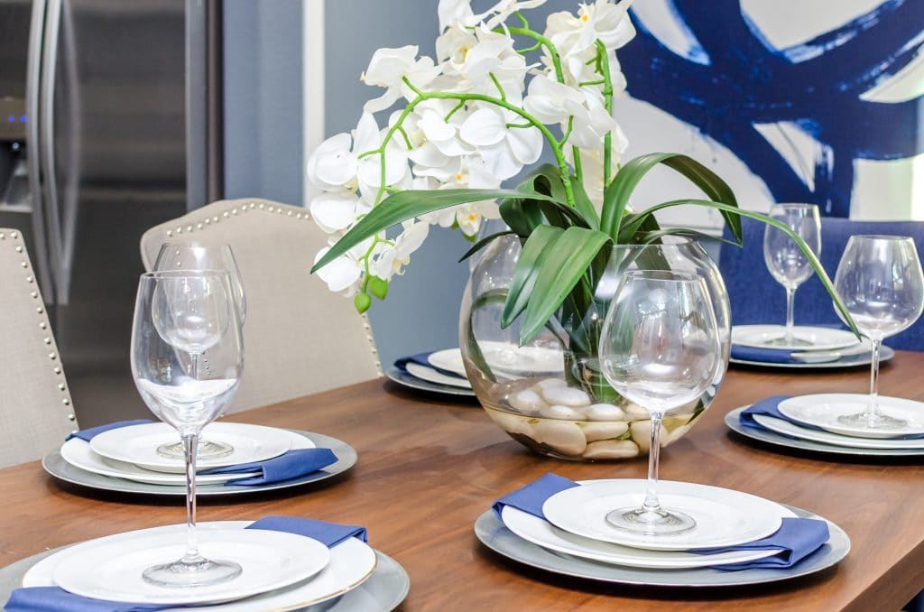 Dining table set with white plates, blue cloth napkins, and a centerpiece with white flowers