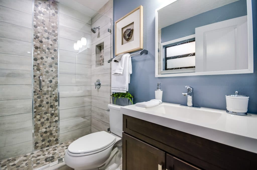 Master bathroom staged with artwork and fresh white towels