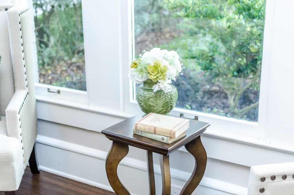 Vase with flowers and two stacked books on a small end table