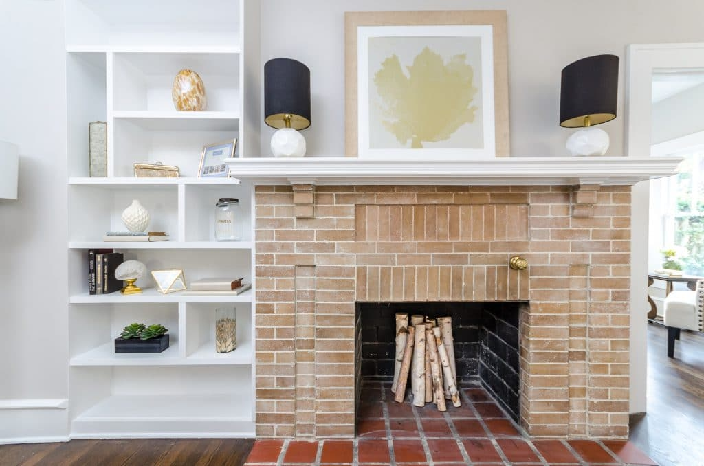 Brick fireplace with built-in shelving to the left