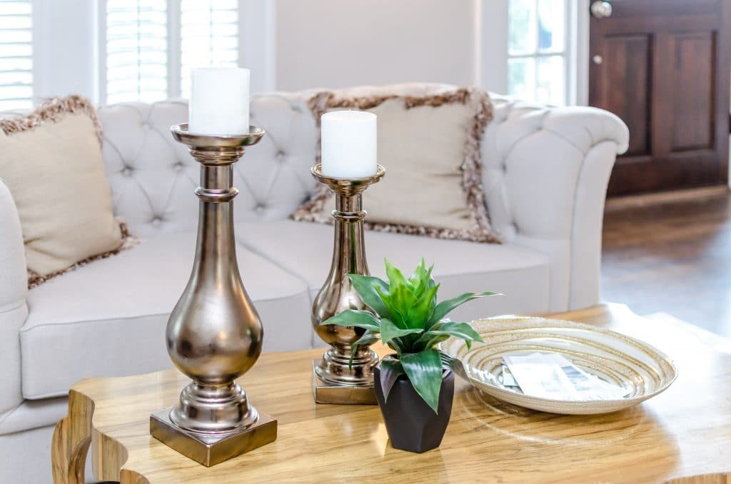 Candlesticks and a succulent in a vase on a coffee table