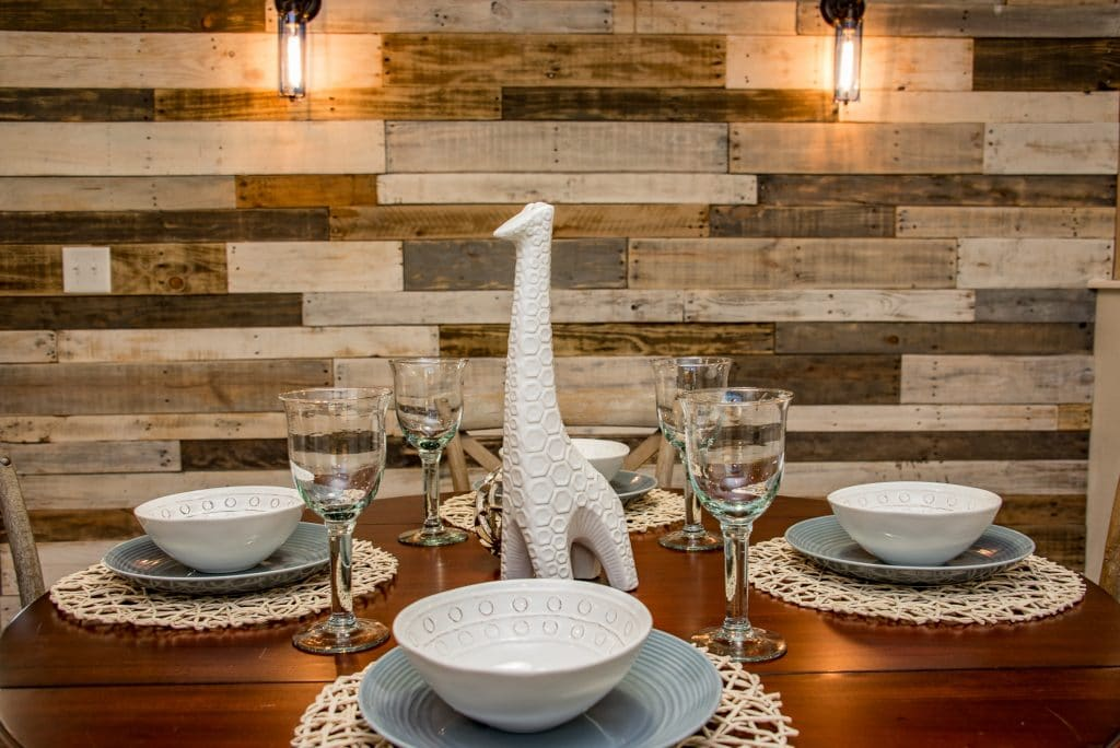 Table set with a white giraffe statue centerpiece in front of an accent wall decorated with reclaimed wood in the breakfast nook of the house on Zombie House Flipping season two episode eleven