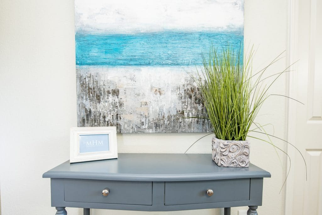 Small entry table with artwork in the foyer