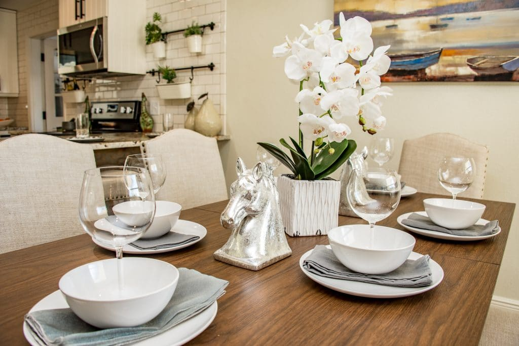 Dining room table set with an orchid centerpiece and silver horse bust