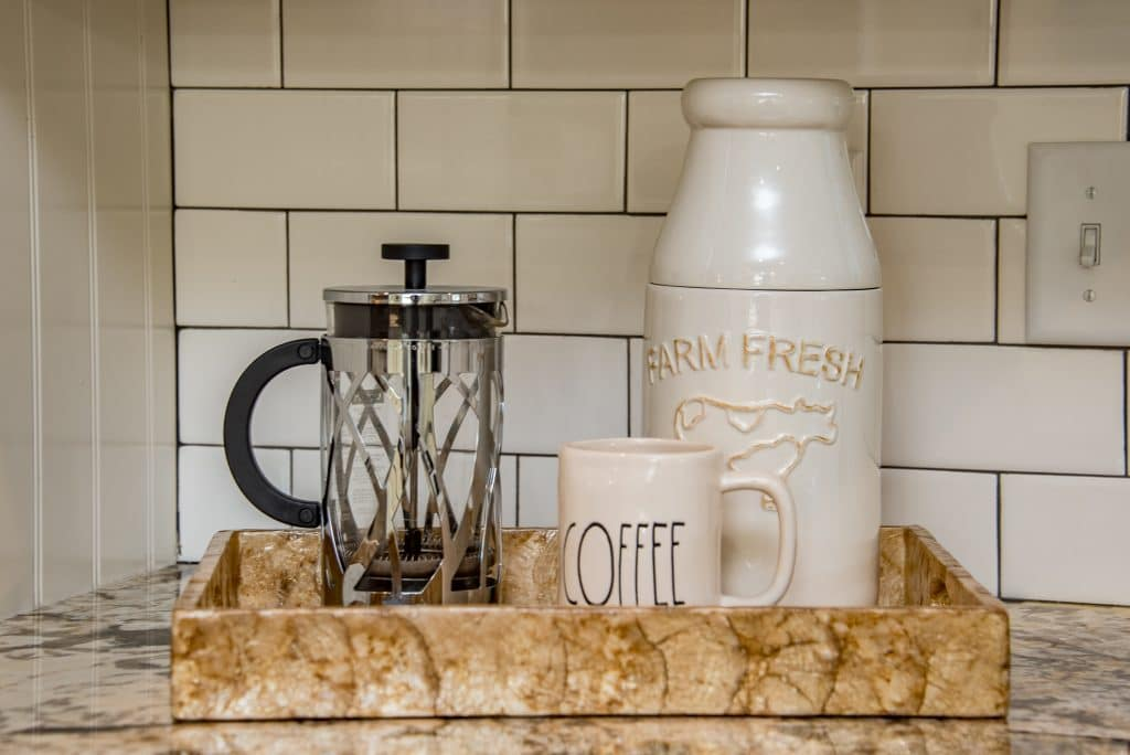 French press, mug, and ceramic milk container placed inside a decorative tray on top of the kitchen counter