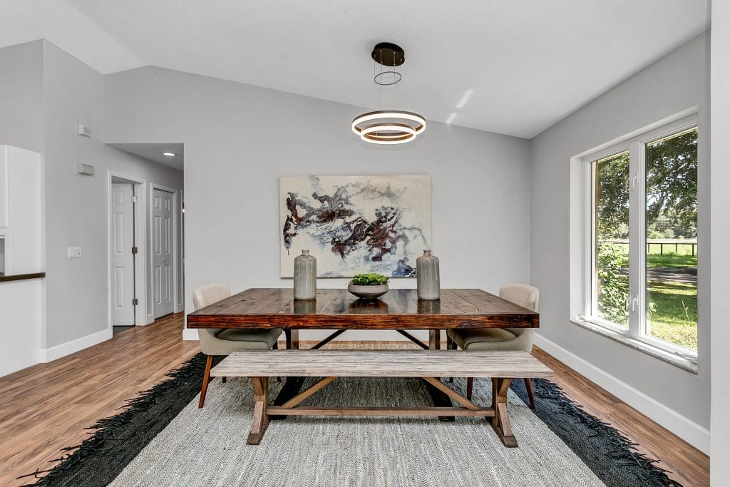 Dining room staged with a simple wooden table and neutral toned seating.