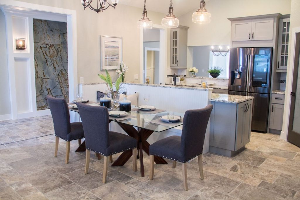 Dining and kitchen area with Parson dining chairs, a set table with wine glasses, and artwork hanging.