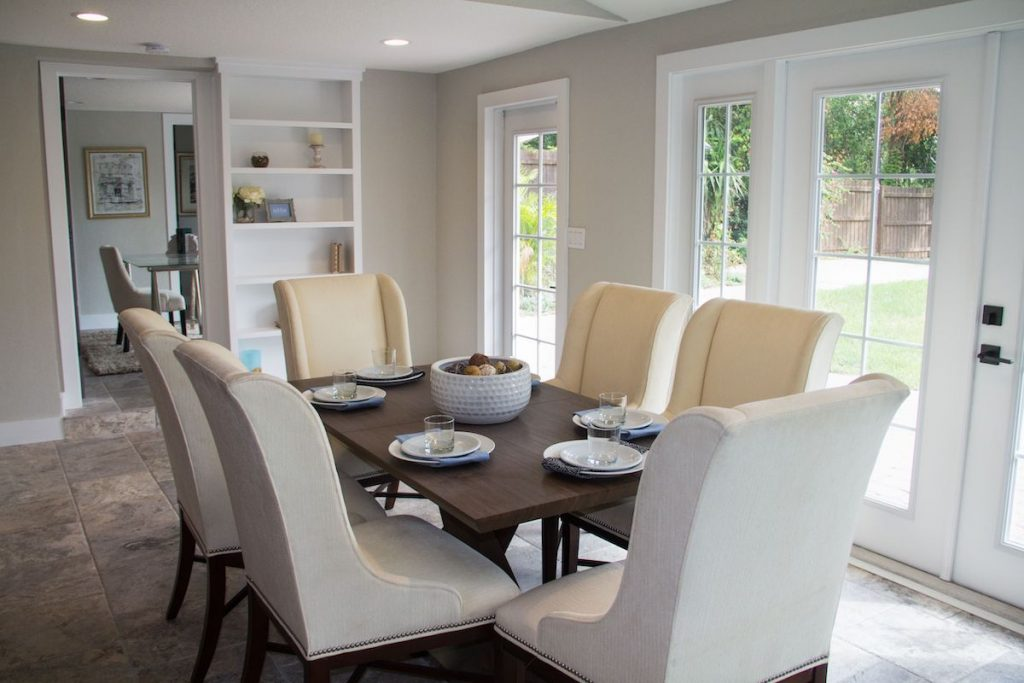 Formal dining room of the house featured on Zombie House Flipping season two episode thirteen, containing French doors, a dining set with large neutral dining chairs, place settings, and a built in bookshelf nearby.