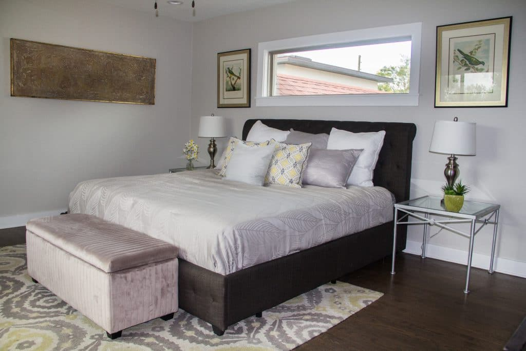 Master bedroom of the house featured in Zombie House Flipping season two episode thirteen, staged with a dark bed frame and light, neutral colored bedding