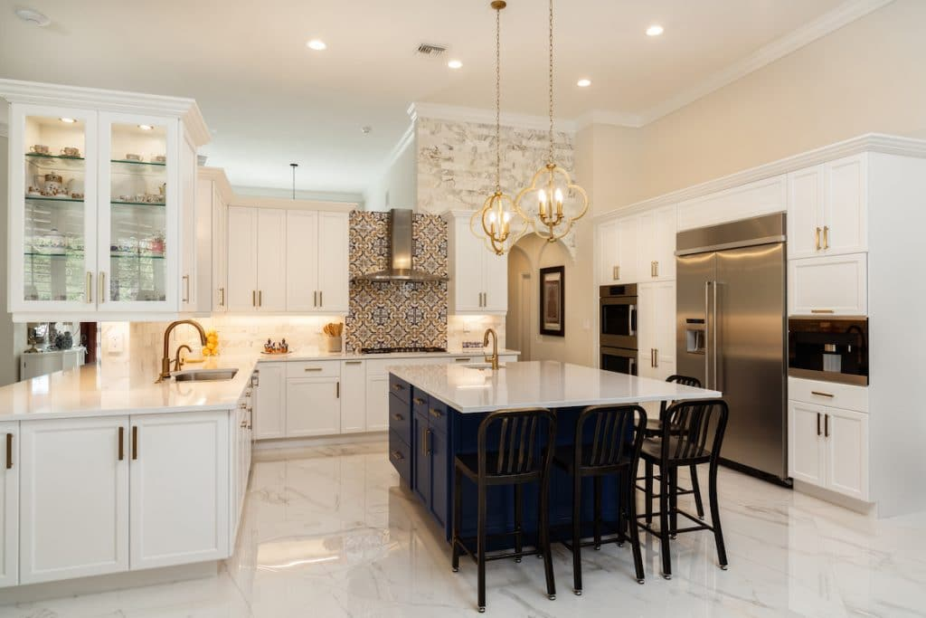 An all-white kitchen with Aesthetic White walls, white cabinetry, and gold details.