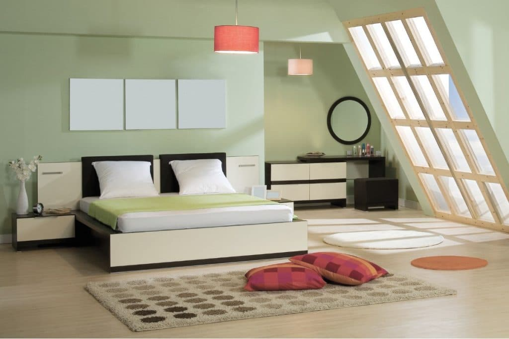 Light green bedroom with red light fixture and red accent pillows