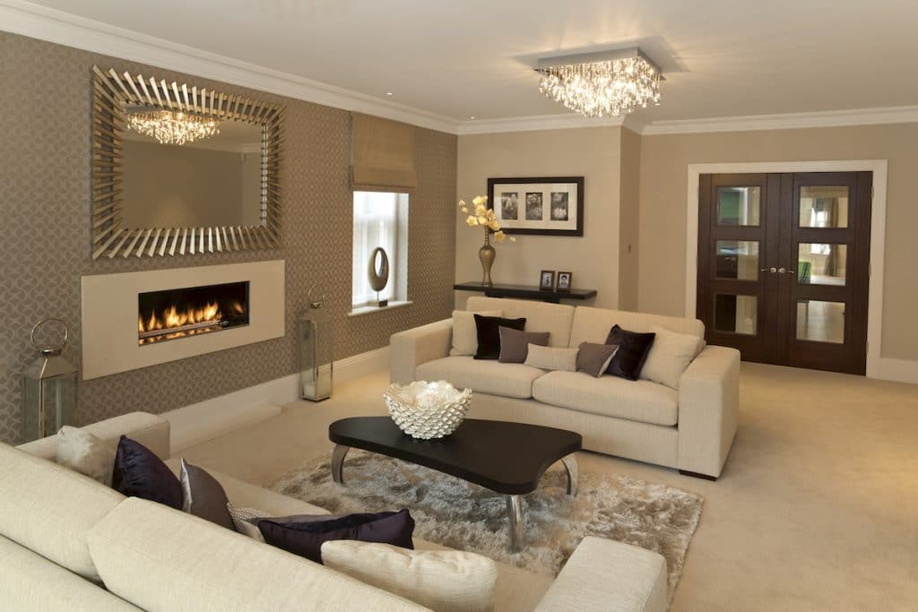 A luxury style living room with beige walls, two sofas, coffee table, and built-in fireplace.