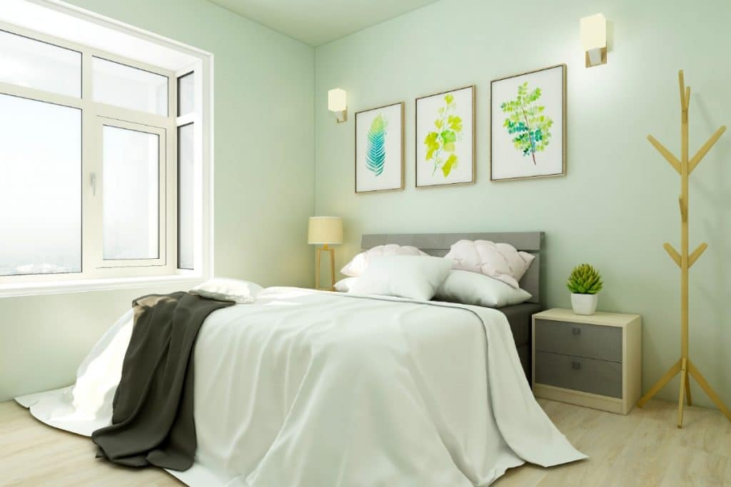 Bedroom painted with Enlightened Lime featuring three art pieces hanging over the headboard and a natural wood coat rack