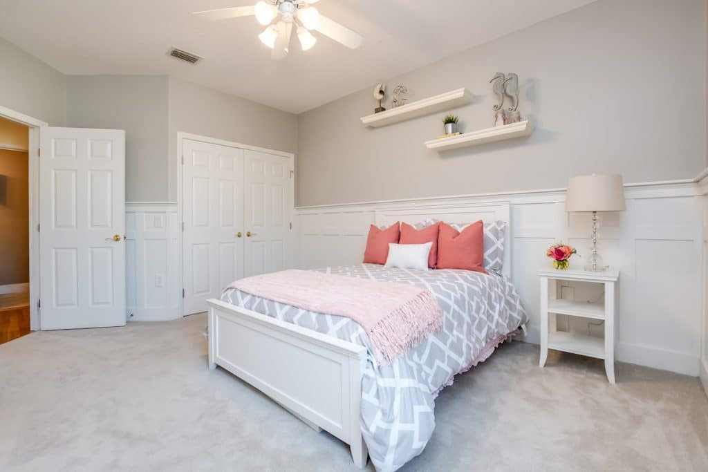 Bedroom with coral accents like throw pillows and blanket.