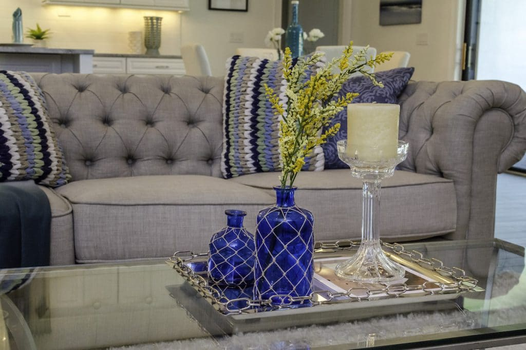 Close up of a living room sofa and coffee table with decorative display: vases, flowers, and a candle.