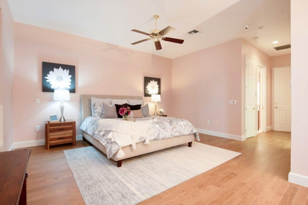Bedroom with coral walls, wood floors, and wooden nightstands.