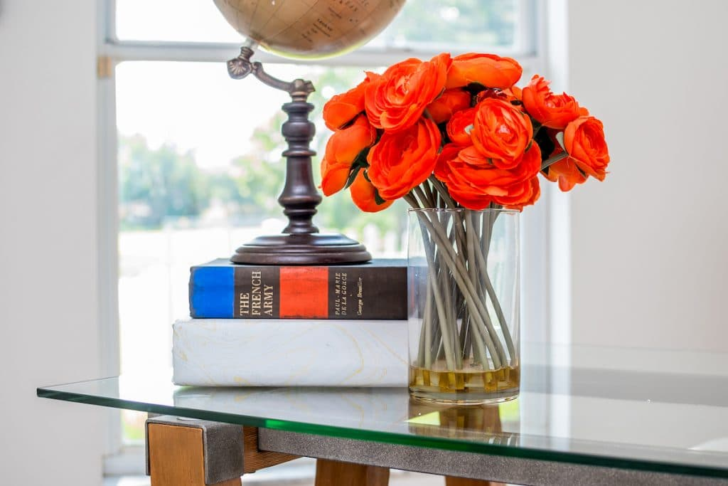 Close up of stacked books, a globe, and a vase of orange flowers.
