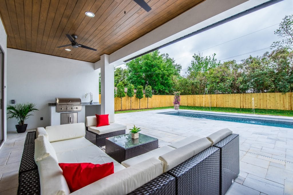 Patio area with patio furniture, grill, and a pool.