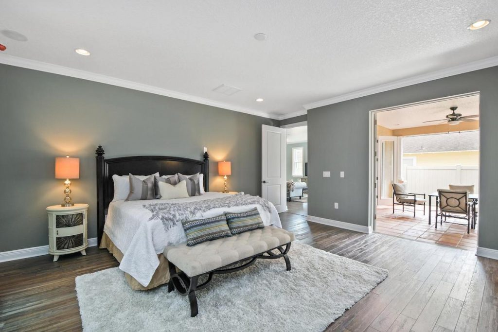 A master bedroom with rug, bedroom bench, and nightstands.