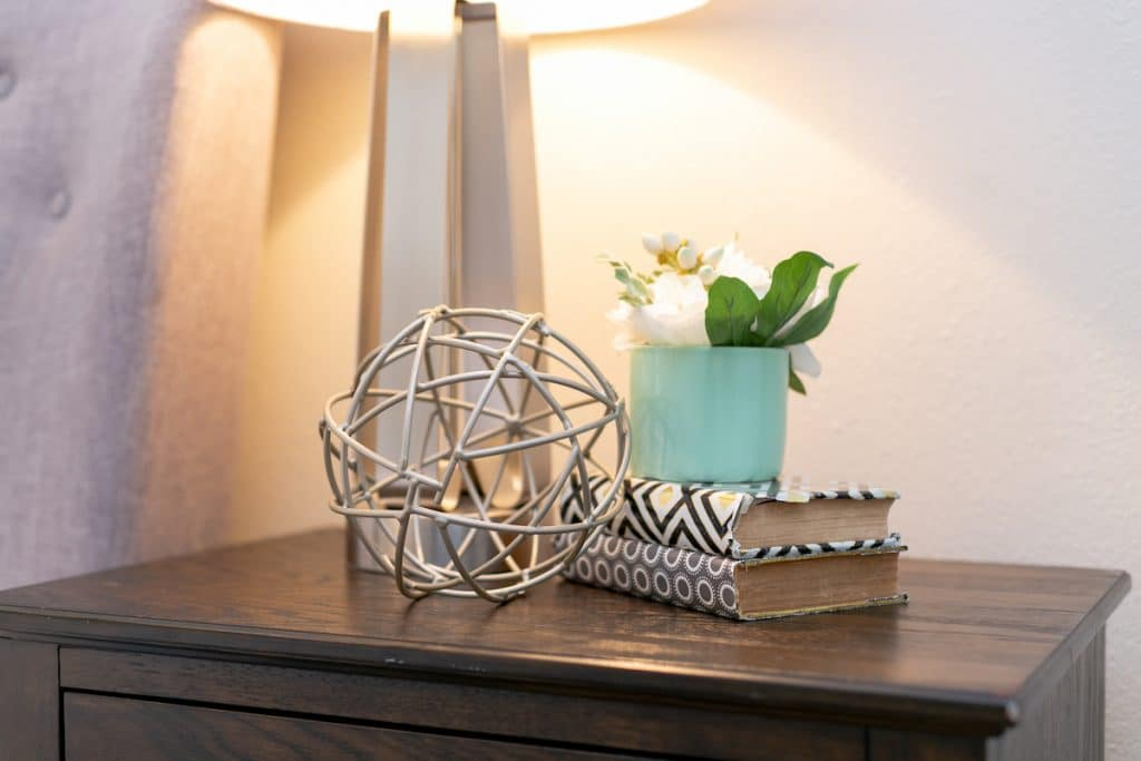 Closeup of a nightstand display including stacked books, flowers, and a decorative sphere sculpture.