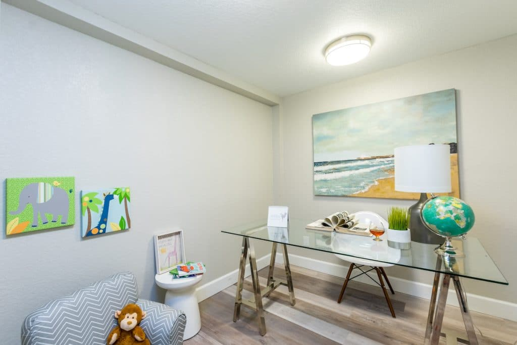 A room that is part office, part playroom with children themed artwork and painted beach canvas staged by MHM Professional Staging for Zombie House Flipping season three episode one.