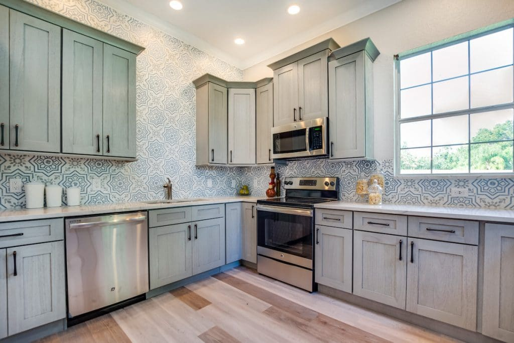 Kitchen with beautiful blue patterned tile staged by MHM Professional Staging for Zombie House Flipping season three episode one.