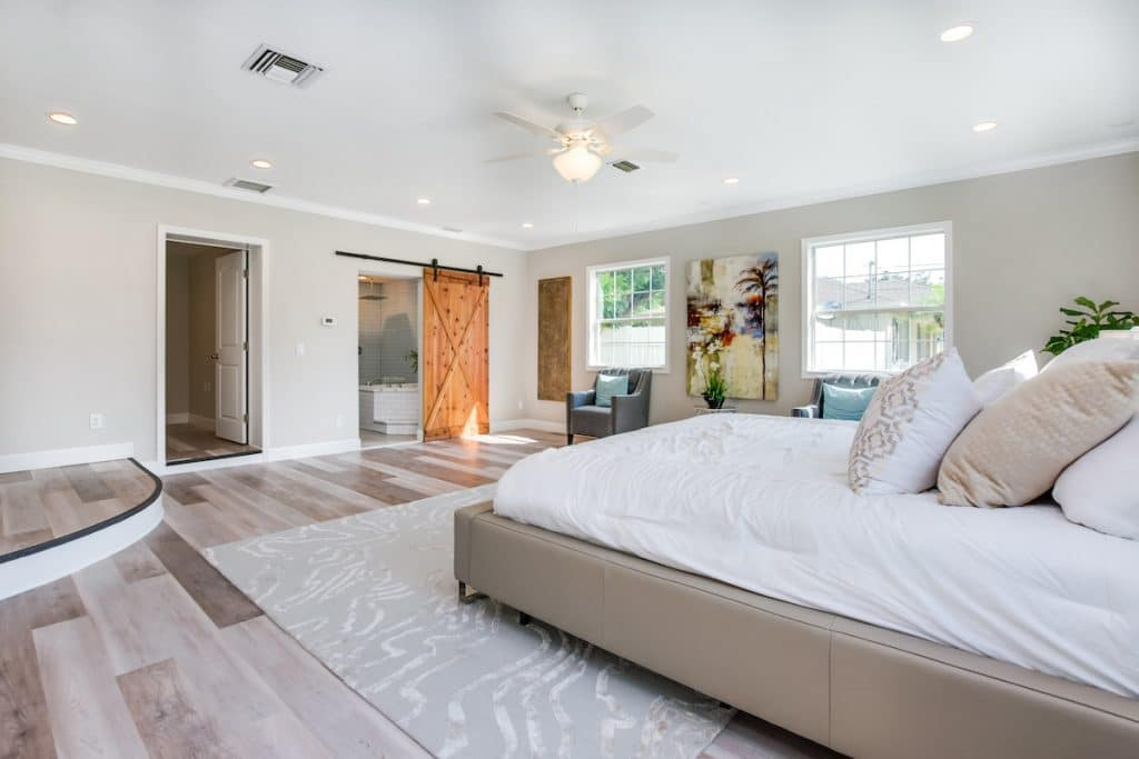 Another view of master bedroom with visible sliding barn door staged by MHM Professional Staging for Zombie House Flipping season three episode one.