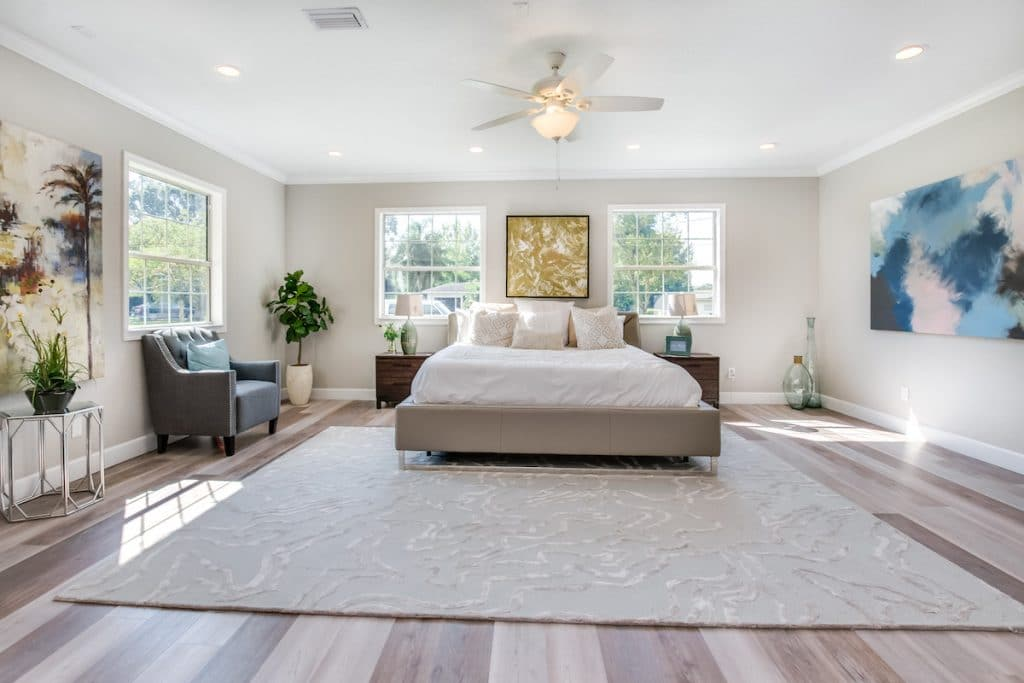 Spacious master bedroom with large rug, bed, armchair, nightstands, and artwork staged by MHM Professional Staging for Zombie House Flipping season three episode one.