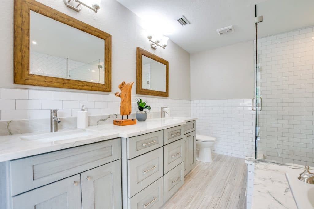 Master bathroom counter top with double sinks, wooden mirrors, wooden decor, and a plant staged by MHM Professional Staging for Zombie House Flipping season three episode one.