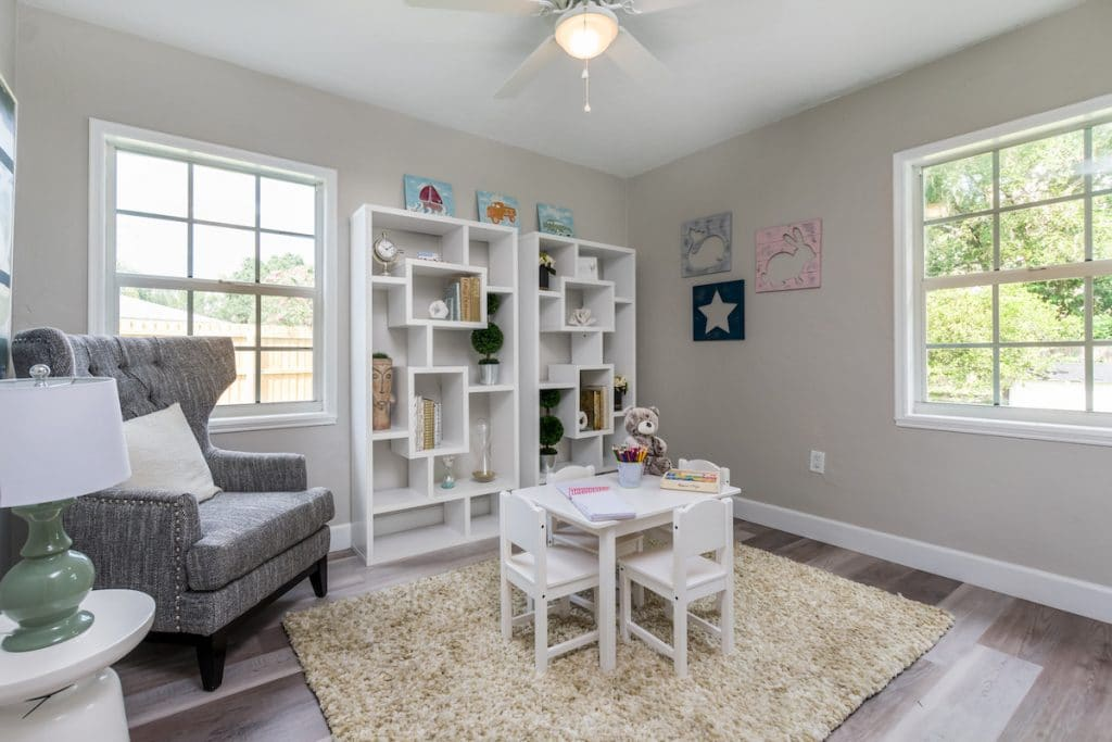 Small bedroom with light colored children's furniture.