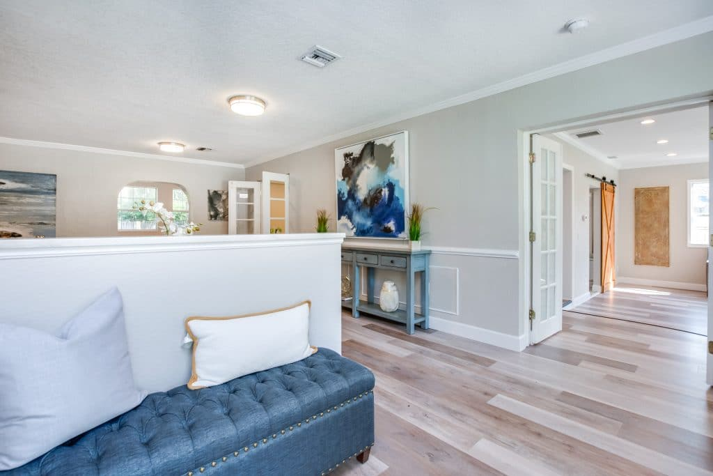 View of home through entryway with tufted blue bench with throw pillows staged by MHM Professional Staging for Zombie House Flipping season three episode one.