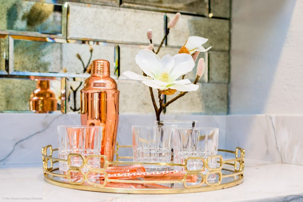 A drink tray with classy glassware and drink accessories.