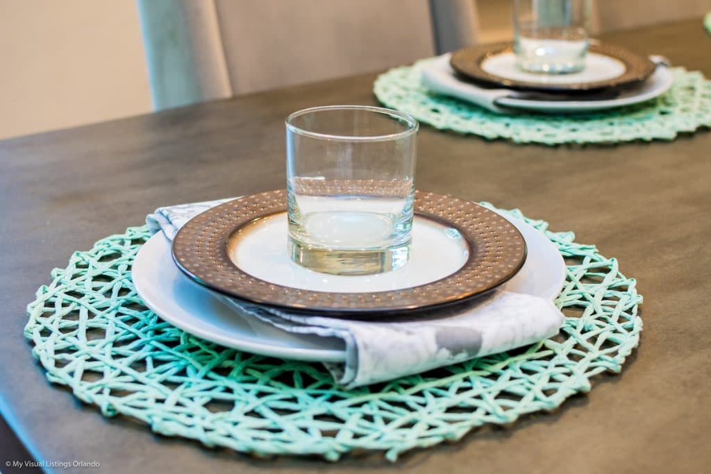 A close up of table setting: placemat, stacked plates, and a glass.