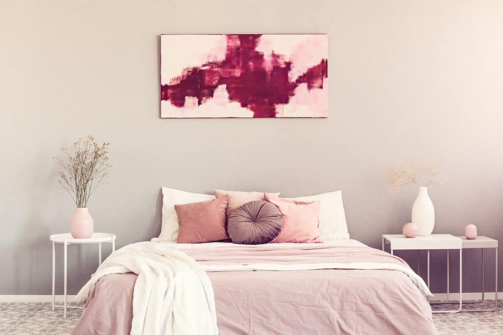Bedroom with light coral accents like bedspread and vases.